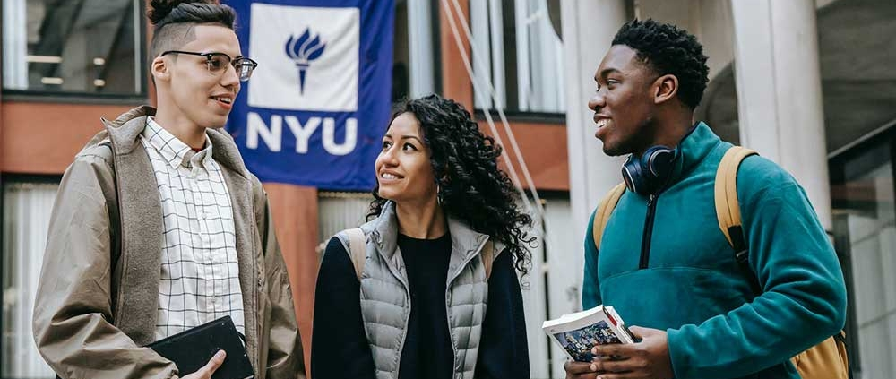 three college students talking and NYU flag in background